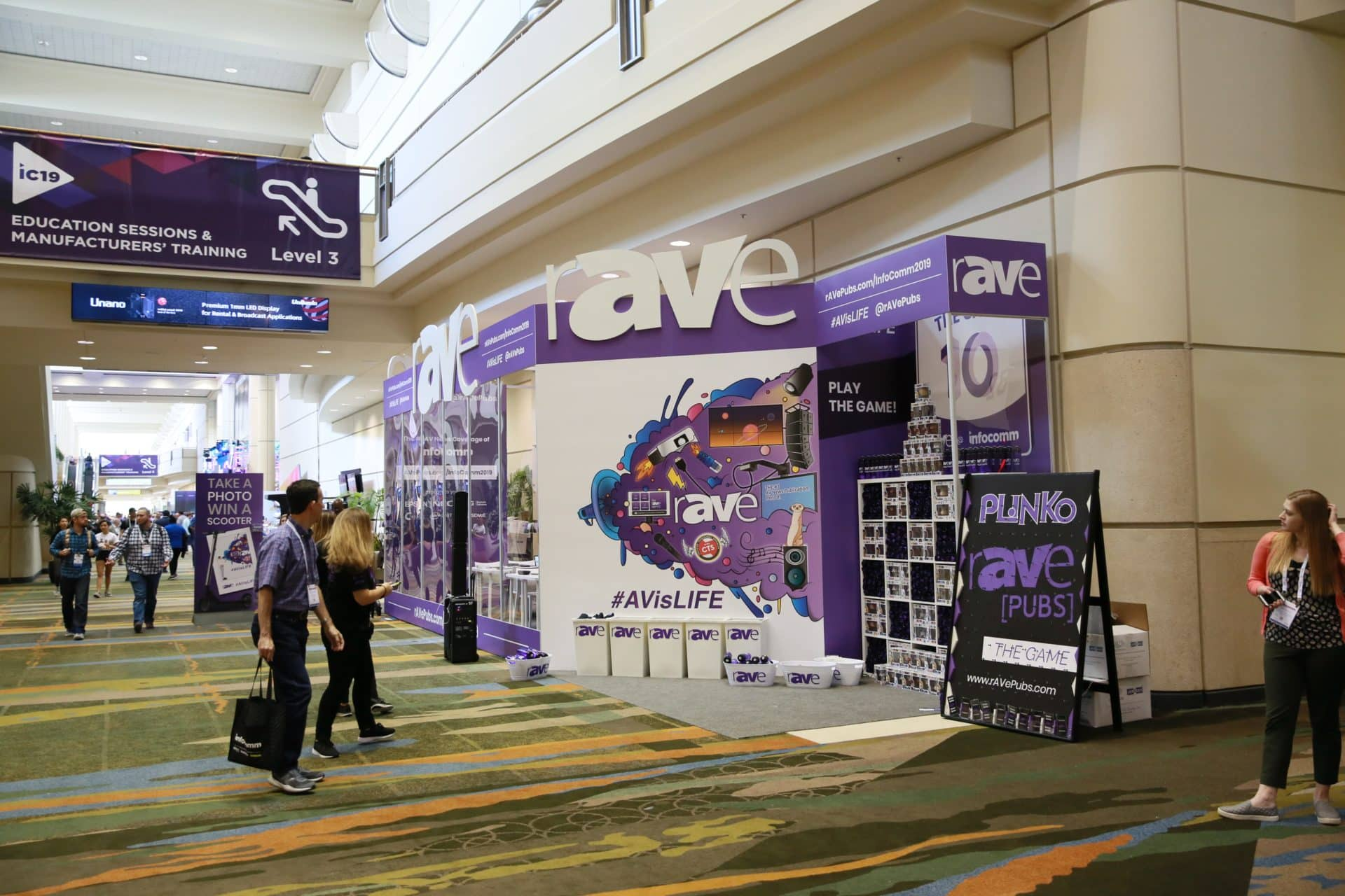 People walk past the rAVe Booth at InfoComm 2019 in Orlando, Florida